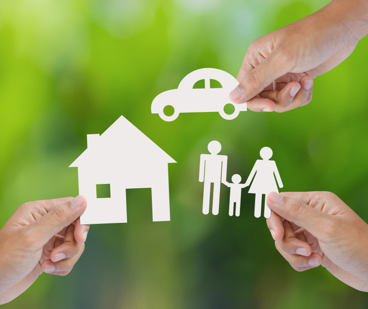 Hands holding up cutouts of a car, family, and house